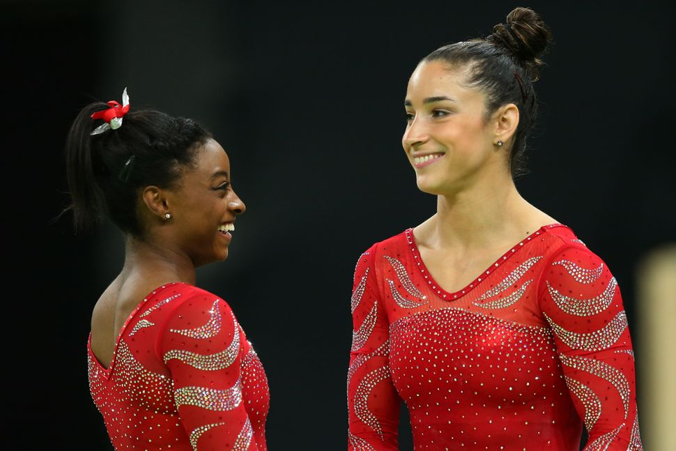 Aly Raisman and Simone Biles look on during an artistic gymnastics training session on August 4, 2016 at the Arena Olimpica d