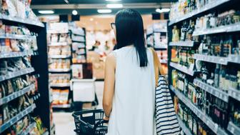 Young woman walking along the grocery aisle in a supermarket shopping for daily necessities and groceries.