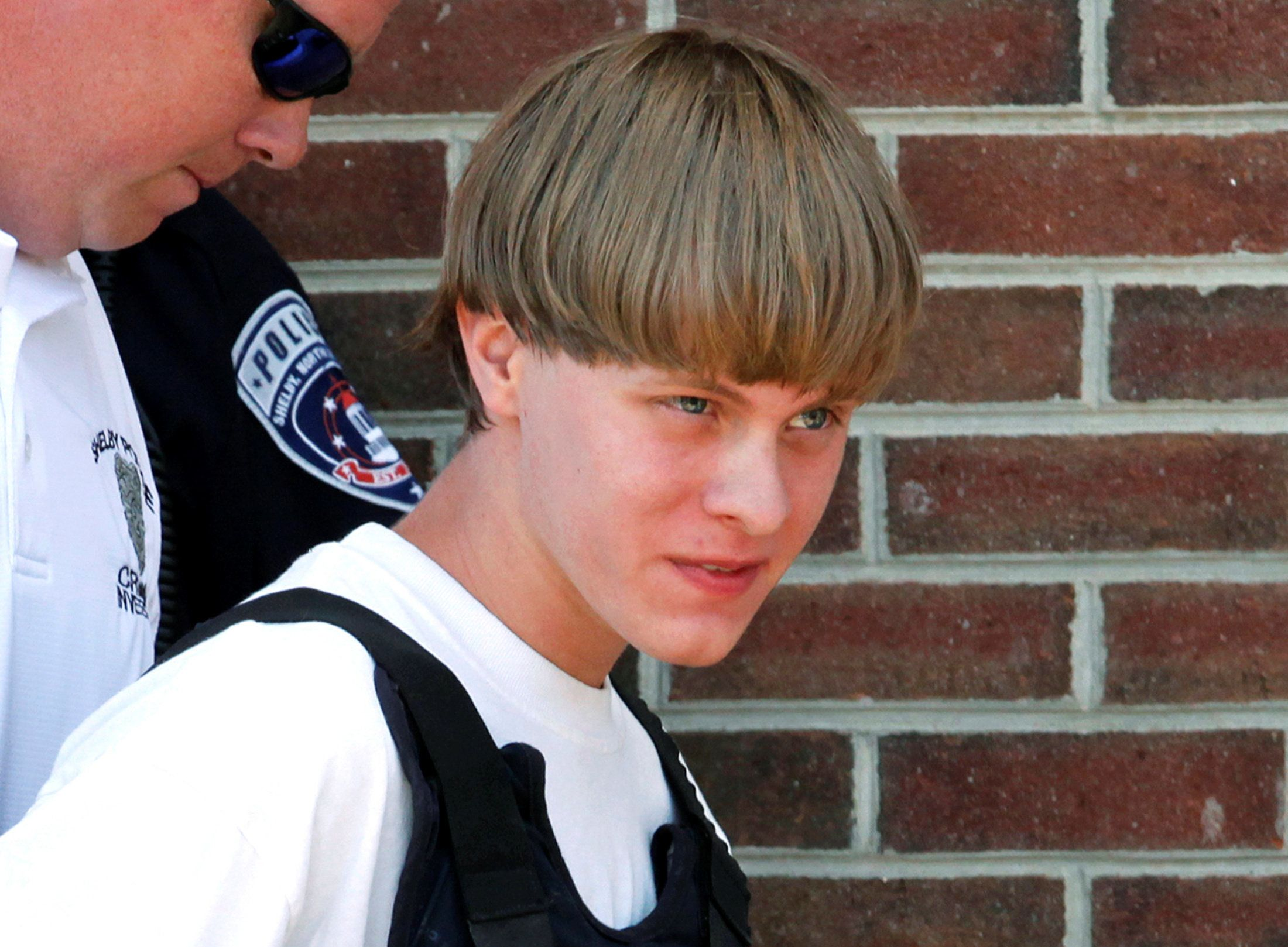 Police lead Dylann Roof into the courthouse in Shelby, North Carolina, where he was arrested the...