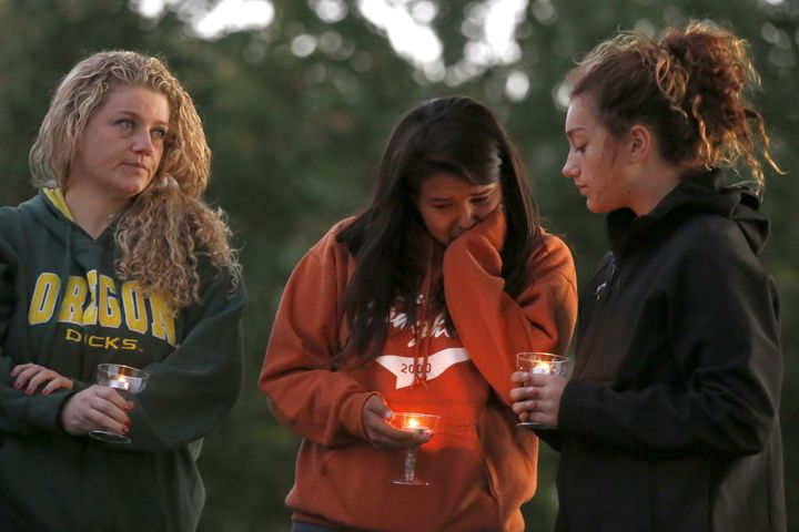 People take part in a candlelight vigil for victims of the Umpqua Community College shooting.