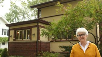 In this Monday, Oct. 5, 2015, photo, retired teacher Linda McQuillen stands in front of her home designed by the famous architect Frank Lloyd Wright in Madison, Wis. Wright experts on Tuesday were expected to reveal that the home built in 1917 near the University of Wisconsin campus, is an American System-Built House. That was part of Wrights effort to develop and market well-designed homes for any income level. It's the second time in four months that a Wright house has been rediscovered in Wisconsin. (AP Photo/Carrie Antlfinger)