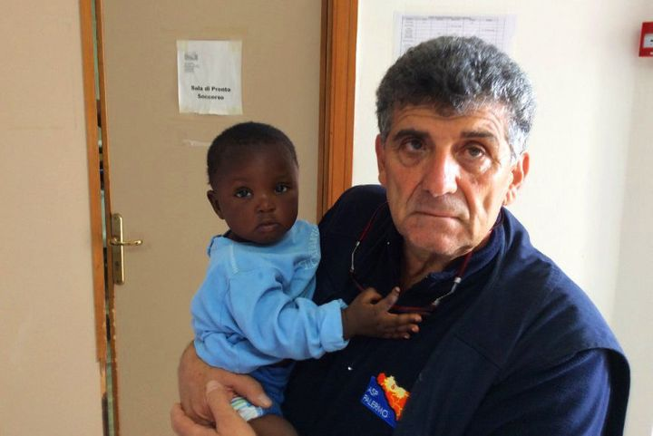 Bartolo holds a 9-month-old Nigerian girl named Favour.