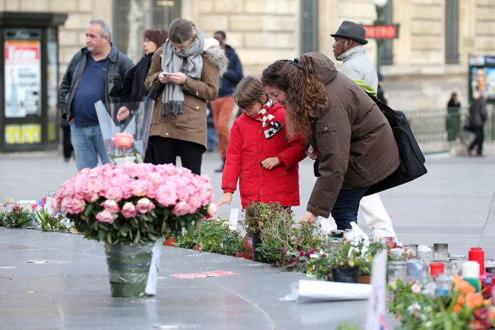Pink flowers are left as people gather at Republique Square near tributes on Jan. 13, 2016, in Paris, France.