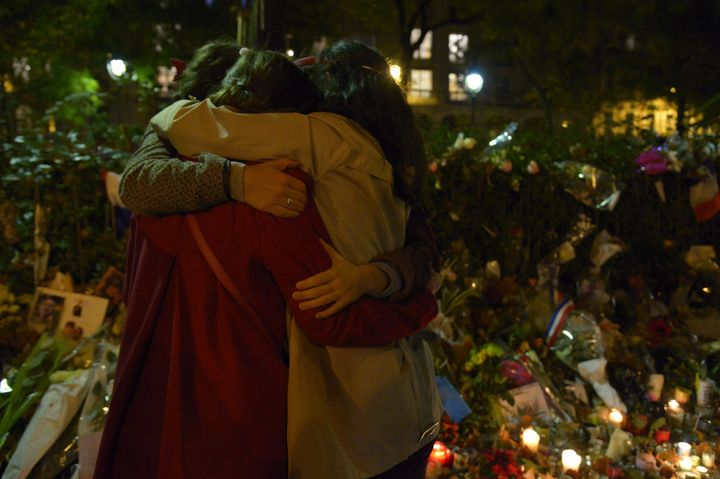 People hug in front of a memorial set-up near the Bataclan theatre in Paris.