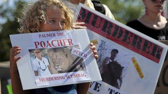 Protesters hold signs during a rally outside the River Bluff Dental clinic against the killing of a famous lion in Zimbabwe, in Bloomington, Minnesota July 29, 2015. Wildlife officials on Tuesday accused American hunter Walter Palmer of killing Cecil, one of the oldest and most famous lions in Zimbabwe, without a permit after paying $50,000 to two people who lured the beast to its death. As of Tuesday, Palmer had temporarily closed his office, River Bluff Dental, in Bloomington, Minnesota, amid wishes for his death and widespread criticism of his hunting on social media and under business reviews on Google and Yelp.  REUTERS/Eric Miller