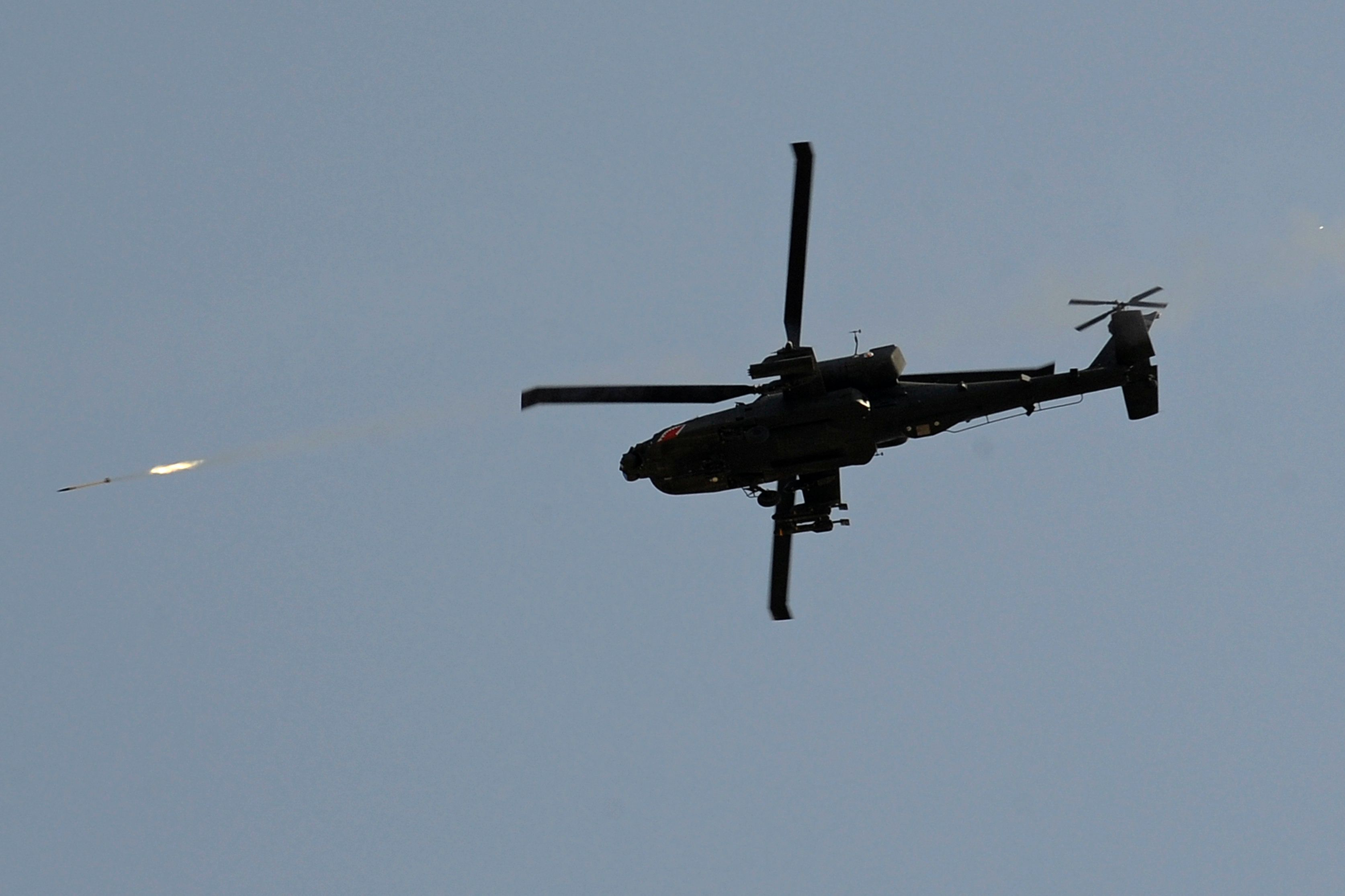 A US Army AH-64 Apache attack helicopter fires a rocket while providing security cover around the area where US soldiers from 703rd EOD Company, 2nd Platoon, Team 6, prepared a controlled detonation of munitions outside Camp Clark in Mandozai district, Khost province, eastern Afghanistan on July 4, 2011. Top US lawmakers on July 3 slammed President Barack Obama's military drawdown plans for Afghanistan as 'risky', unsupported by his military commanders and a threat to progress made in the last year. AFP PHOTO/TED ALJIBE (Photo credit should read TED ALJIBE/AFP/Getty Images)