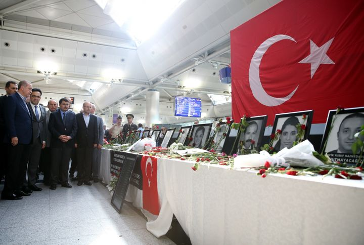 Turkey's President Recep Tayyip Erdogan, left, visits Ataturk Airport in Istanbul on Saturday, where photographs of last week