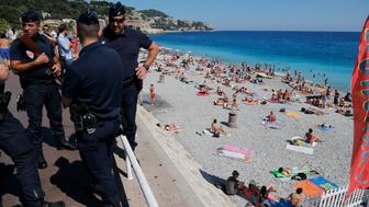 French CRS police patrol on the walkway above a public beach with sunbathers as security measures continue after the Bastille Day truck attack by a driver who ran into a crowd on the Promenade des Anglais that killed scores and injured as many, in Nice, France, July 17, 2016.   REUTERS/Pascal Rossignol
