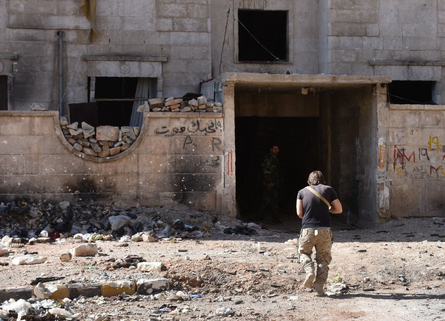 A Syrian pro-government soldier runs for cover in the '1070' apartment block area, south of al-Hamdaniyah,...