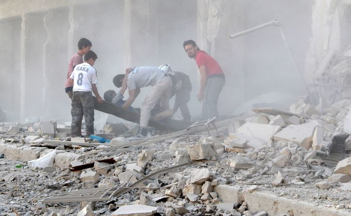 Search and rescue team members evacuate casualties from the rubbles after the Syrian regime forces airstrikes hit Aleppo's op