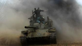 Sudanese Armed Forces (SAF) and Rapid Support Forces (RSF) personnel ride on a tank after recapturing the Daldako area, outside the military headquarters in Kadogli May 20, 2014. The SAF had recaptured the Daldako area, east of the South Kordofan state capital of Kadogli, from rebels, according to media reports quoting the SAF on Sunday. REUTERS/Mohamed Nureldin Abdallah (SUDAN - Tags: POLITICS CIVIL UNREST MILITARY)