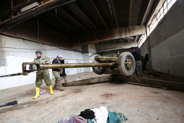 Rebel fighter clean a weapon in al-Rai town, northern Aleppo countryside, Syria December 25,