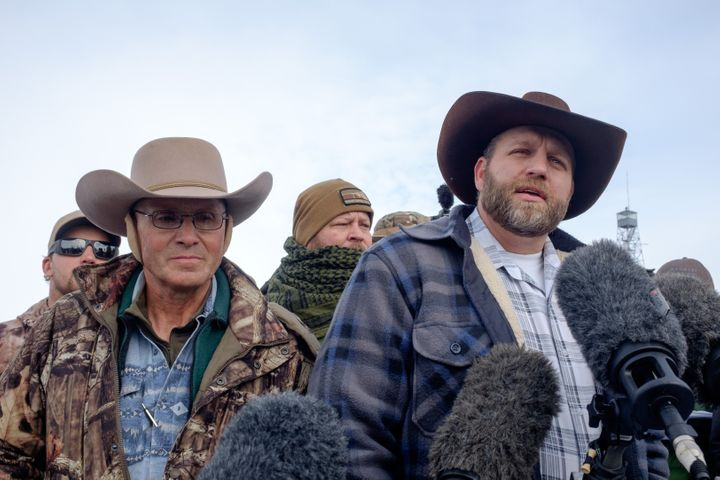 Ammon Bundy, right, leader of a group of armed anti-government protesters speaks to the media as other members look on at the