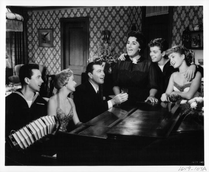 Vic Damone, Jane Powell, Tony Martin, Kay Armen, Russ Tamblyn and Debbie Reynolds gathered around a piano singing in a scene