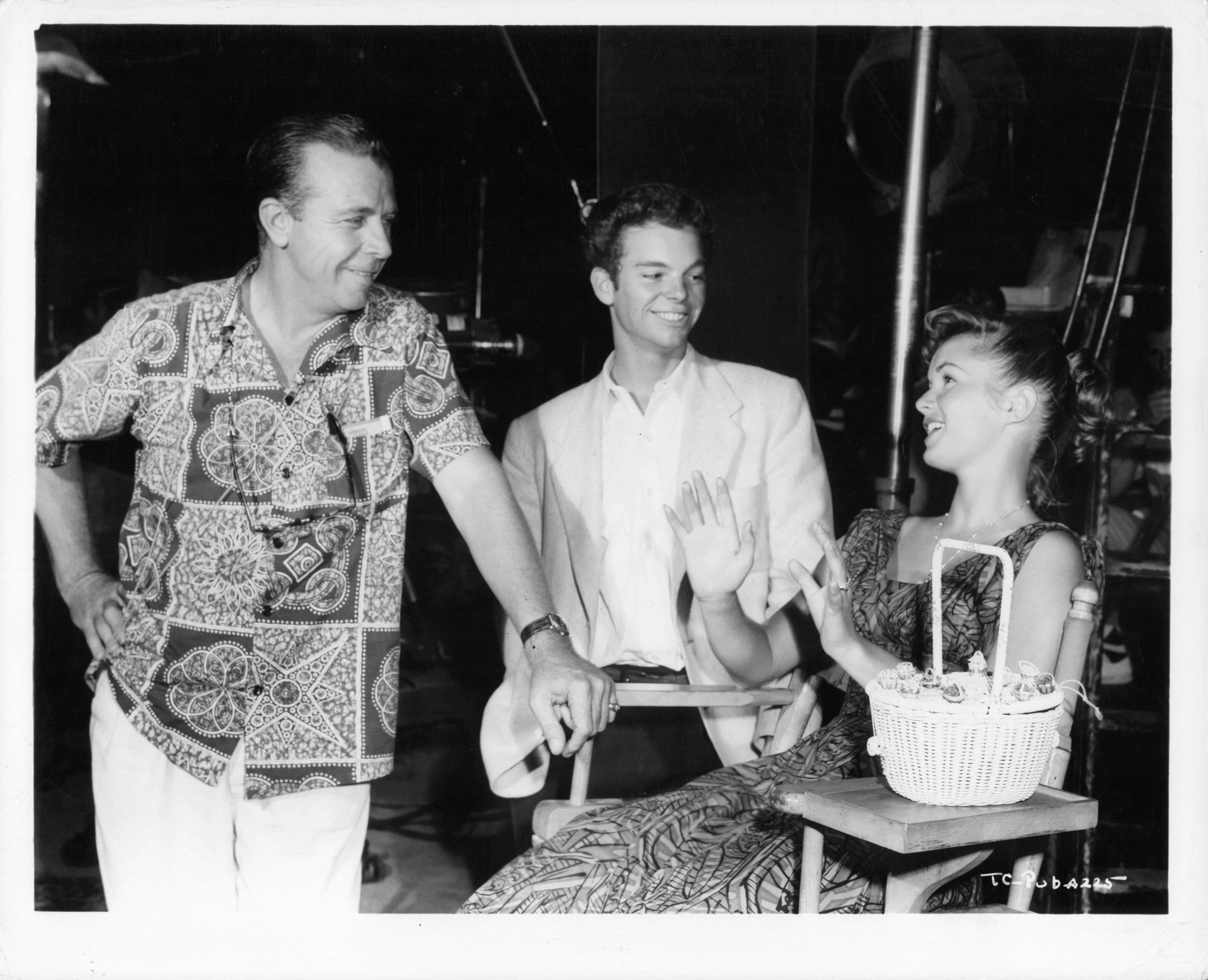 """Dick Powell talks with Russ Tamblyn and Debbie Reynolds during a break from shooting the film """"The Enemy Below,"""" 1957."""