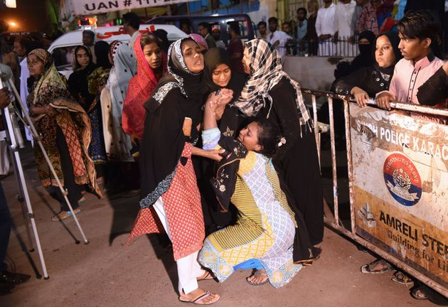 Pakistani women mourn relatives outside of a mortuary in Karachi onSaturdayfollowing a suicide...