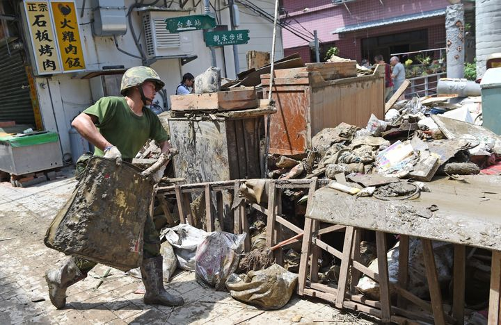 A military soldier helps clearing up debris in Wulai, the New Taipei City, on August 11, 2015.