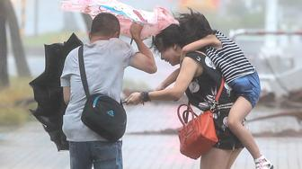 KAOHSIUNG, CHINA - AUGUST 08: (CHINA OUT, TAIWAN OUT) Citizens walk in the Typhoon Soudelor on August 8, 2015 in Kaohsiung, Taiwan of China. Typhoon No. 13 Soudelor hit Fujian on August 8-9 causing 6 death and 5 missing, according to local media. (Photo by Unioncom/VCG via Getty Images)