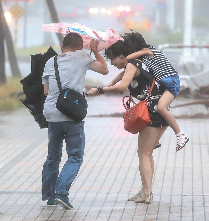 Citizens walk in the Typhoon Soudelor on August 8, 2015 in Kaohsiung, Taiwan of China.