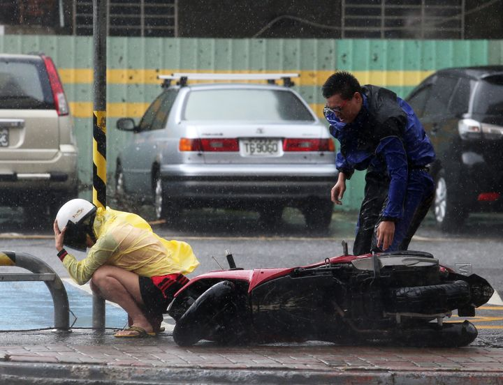 A citizen squats down and hugs an electric line pole beside a motorcycle blown down by Typhoon Soudelor on August 8, 2015 in