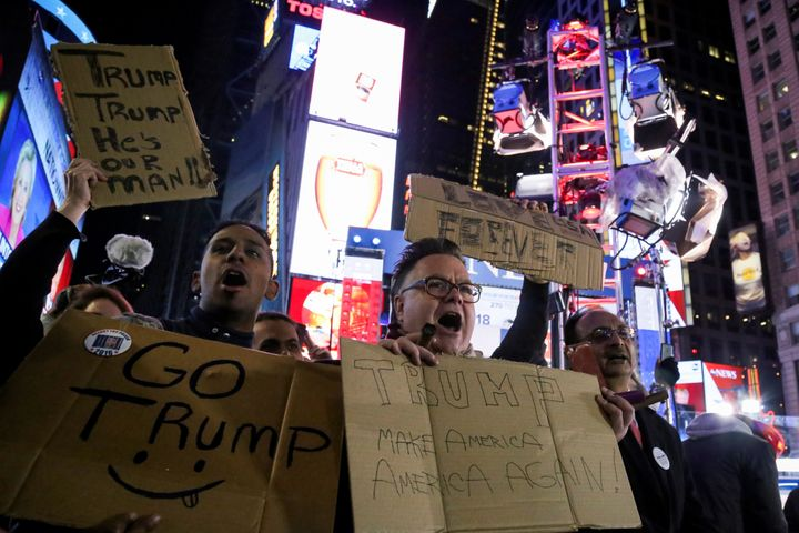 Supporters of U.S. President-elect Donald Trump hold signs as they rally in New York'sTimes Square on Nov. 9, 2016.