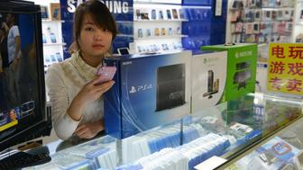 A vendor sells game consoles including Xbox One and Sony's PS4 which they say enter China through unofficial channels in a major electronics market in Shanghai on January 8, 2014. China has formally authorised game consoles made in a new Shanghai free-trade zone (FTZ) to be sold in the country, potentially opening its lucrative market up to the likes of Sony's PlayStation and Microsoft's Xbox.  AFP PHOTO/Peter PARKS        (Photo credit should read PETER PARKS/AFP/Getty Images)