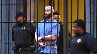 Officials escort 'Serial' podcast subject Adnan Syed from the courthouse on Wednesday, Feb. 3, 2016 following the completion of the first day of hearings for a retrial in Baltimore, Md. (Karl Merton Ferron/Baltimore Sun/TNS via Getty Images)