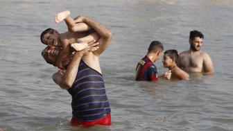 Residents play in the Tigris river to cool off in northern Baghdad's Adhamiya district July 30, 2015. A searing heat wave forecast to sweep through Iraq prompted the government to declare a four-day holiday starting on Thursday and order regular power cuts at state institutions.  REUTERS/Ahmed Saad