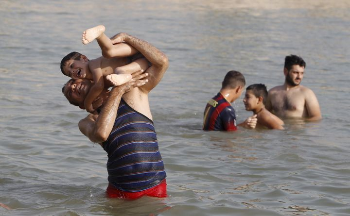 Residents play in the Tigris river to cool off in northern Baghdad's Adhamiya district July 30, 2015.