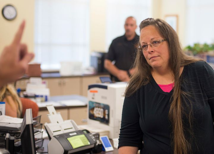 Kim Davis, the Rowan County Clerk of Courts, listens to Robbie Blankenship and Jesse Cruz as they speak with her about gettin