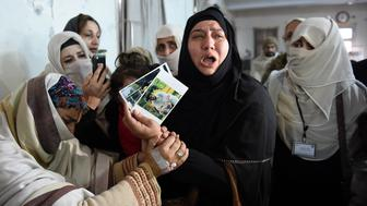 TOPSHOT - A relative of a 2014 Peshawar school attack victim shows her son's pictures to a student victim (L) of the Bacha Khan University attack at a hospital in Charsadda on January 21, 2016. Pakistan observed a day of national mourning Thursday for the 21 people killed when heavily-armed gunmen stormed a university in the troubled northwest, exposing the failings in a national crackdown on extremism. AFP PHOTO / A MAJEED / AFP / A Majeed        (Photo credit should read A MAJEED/AFP/Getty Images)