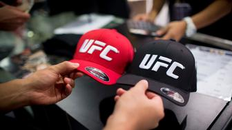 A man browses hats displaying the Ultimate Fighting Championship (UFC) logo at a merchandise kiosk during UFC Fight Night at Cotai Arena, inside the Venetian Macao resort and casino, operated by Sands China Ltd., a unit of Las Vegas Sands Corp., in Macau, China, on Saturday, Aug. 23, 2014. UFC, the largest pay-per-view event provider, broadcasts to more than 800 million homes worldwide. Photographer: Brent Lewin/Bloomberg via Getty Images