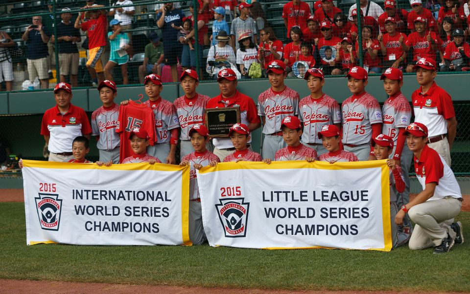 SOUTH WILLAMSPORT, PA - AUGUST 30:  Members of team Japan pose with the championship banner after their 18-11 win over the Mi