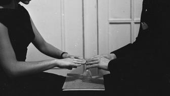 circa 1950:  A medium using a ouija board and glass to communicate with spirits.  (Photo by Orlando /Three Lions/Getty Images)