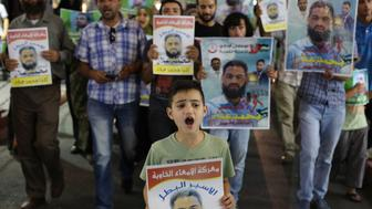 Palestinian protesters take part in a rally in the West Bank city of Ramallah on August 19, 2015, in solidarity with Mohammed Allan (portraits), a Palestinian detainee held without charge in an Israeli jail since November and whose two-month hunger strike has put his life at risk. Israel's High Court suspended the detention-without-trial order on hunger-striking Palestinian prisoner Allan but said he must remain in hospital pending a decision on his future. AFP PHOTO / ABBAS MOMANI        (Photo credit should read ABBAS MOMANI/AFP/Getty Images)