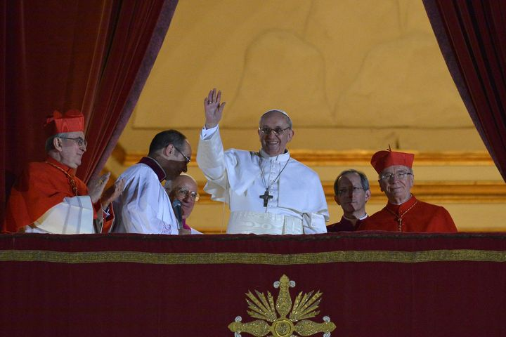 Pope Francis waves to the crowd from the central balcony of St. Peter's Basilica at the Vatican, during his first appearance