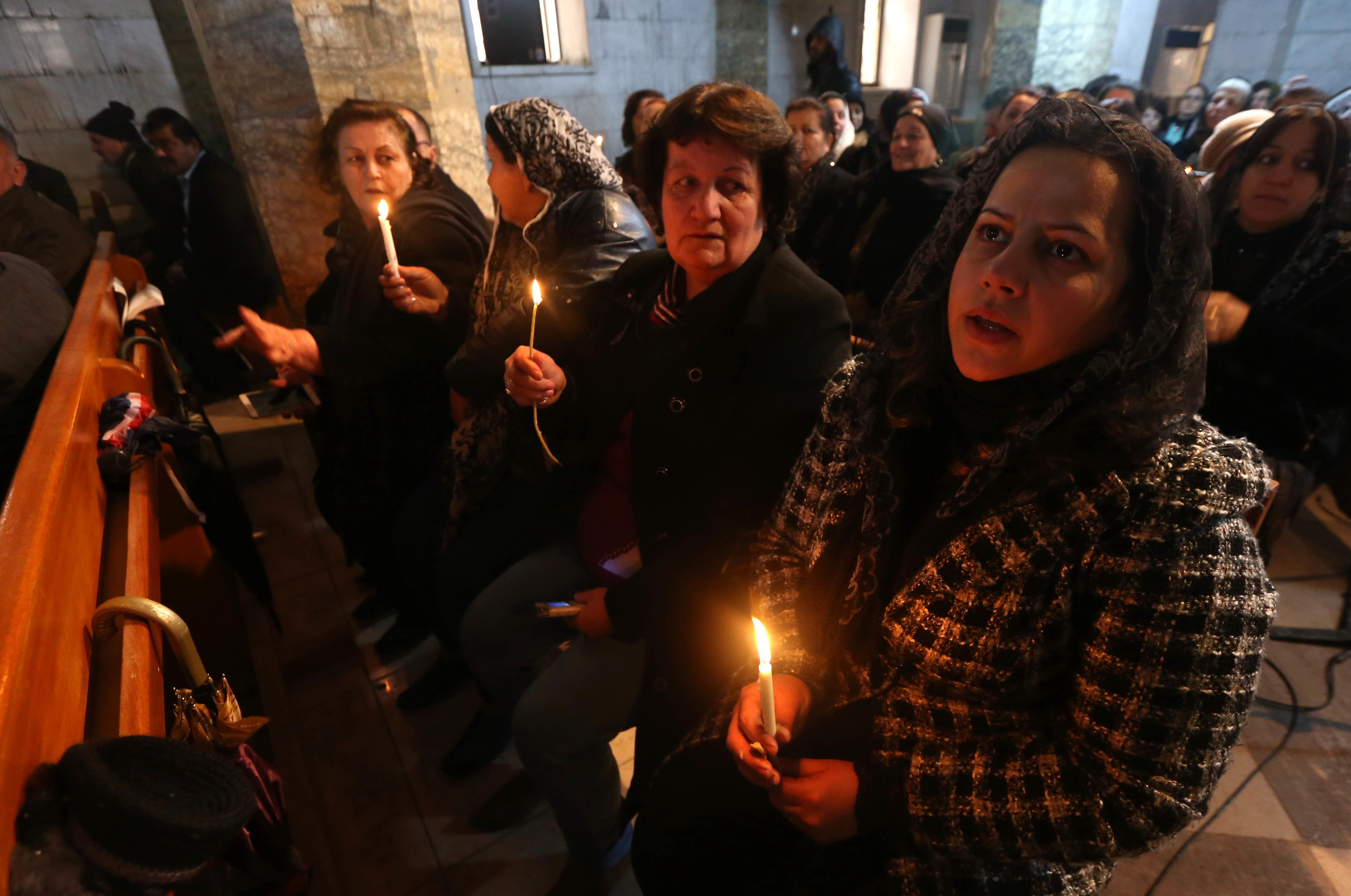 CORRECTION - Iraqi Christians attend a Christmas Eve service at the Mar Shimoni church in the town of Bartalla near Mosul, on December 24, 2016, for the first time since its recapture from Islamic State (IS) jihadists.  IS seized Bartalla and swathes of other territory north and west of Baghdad in the summer of 2014, leaving Christians with the grim choices of conversion, paying a tax, fleeing or death. The town was recaptured as part of the massive military operation to retake Mosul, the last IS-held Iraqi city, which was launched on October 17.   / AFP / SAFIN HAMED / The erroneous mention[s] appearing in the metadata of this photo by SAFIN HAMED has been modified in AFP systems in the following manner: [2016] instead of [2015]. Please immediately remove the erroneous mention[s] from all your online services and delete it (them) from your servers. If you have been authorized by AFP to distribute it (them) to third parties, please ensure that the same actions are carried out by them. Failure to promptly comply with these instructions will entail liability on your part for any continued or post notification usage. Therefore we thank you very much for all your attention and prompt action. We are sorry for the inconvenience this notification may cause and remain at your disposal for any further information you may require.        (Photo credit should read SAFIN HAMED/AFP/Getty Images)