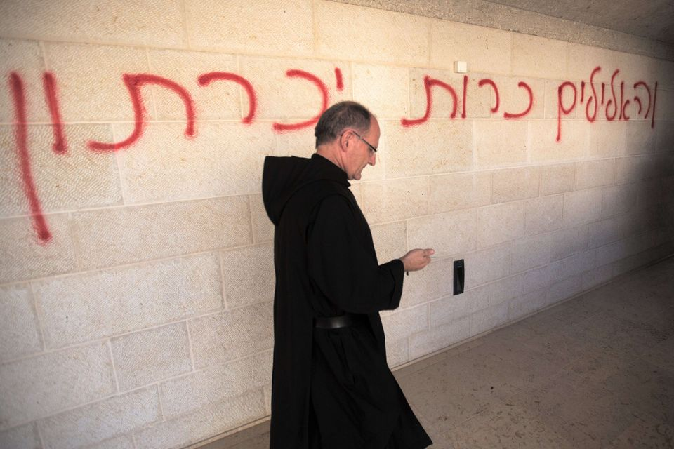A priest walks past a graffiti reading in Hebrew 'idols will be cast out' as he inspects the damage at the Church of the Mult