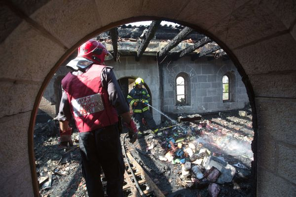Firemen spray water on debris at a room located on the complex of the Church of the Multiplication at Tabgha, on the shores o