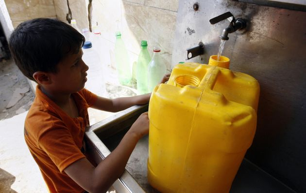 A Palestinian child fills his container in anticipation of water shortages in Rafah, Gaza Strip, on Aug....