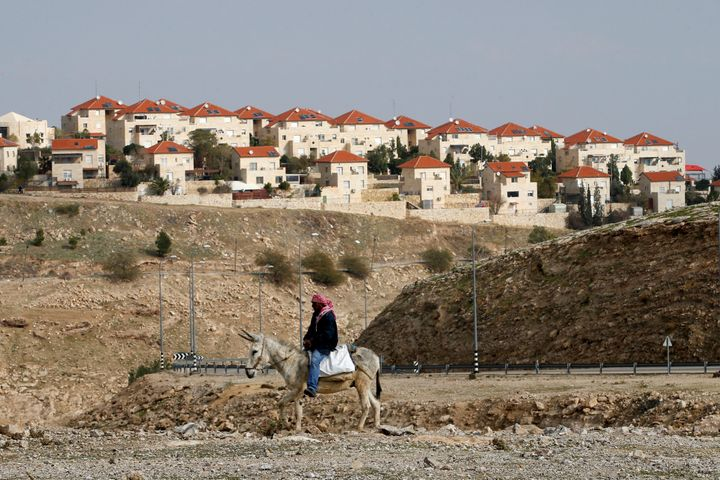 A Palestinian man passes an Israeli settlement in the West Bank on Dec. 28, 2016.