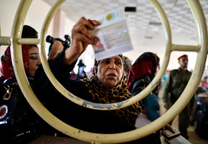 A Palestinian woman shows her identification card at a checkpoint at the border with Egypt on Sept. 7, 2016.