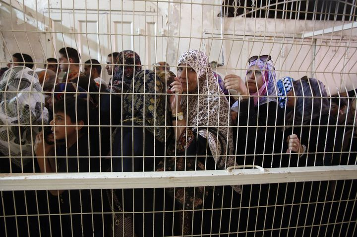 Palestinian Muslims wait at an Israeli checkpoint in Hebron, West Bank on July 1, 2016.