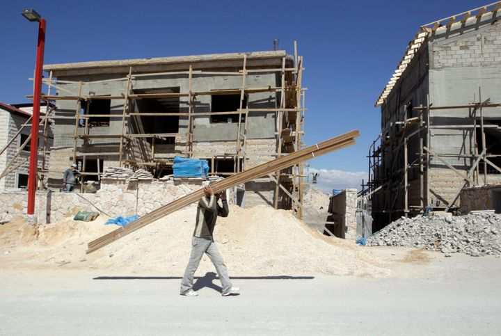 A Palestinian worker carries wood through a construction site in an Israeli settlement in the West Bank on March 13, 2011.