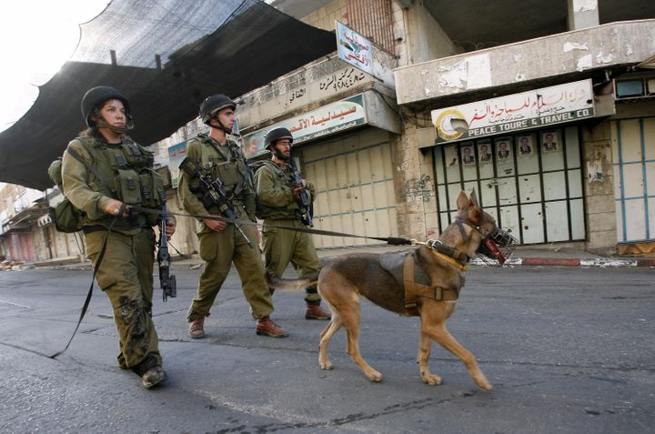 Israeli soldier patrols an empty street following the implementation of a curfew in Hebron, West Bank, in July 2009.
