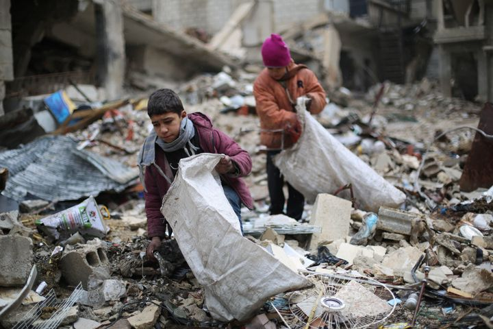 Syrian youths collect wood from rubble to be used for heating and cooking on Dec. 27in Damascus, where residents have g