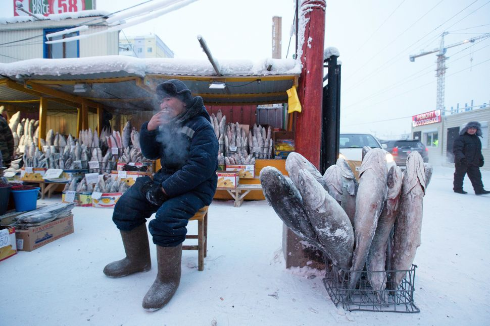 A food vendor sits beside a basket of frozen fish in the Krestyansky open air market in Yakutsk, Russia, on Feb. 17.