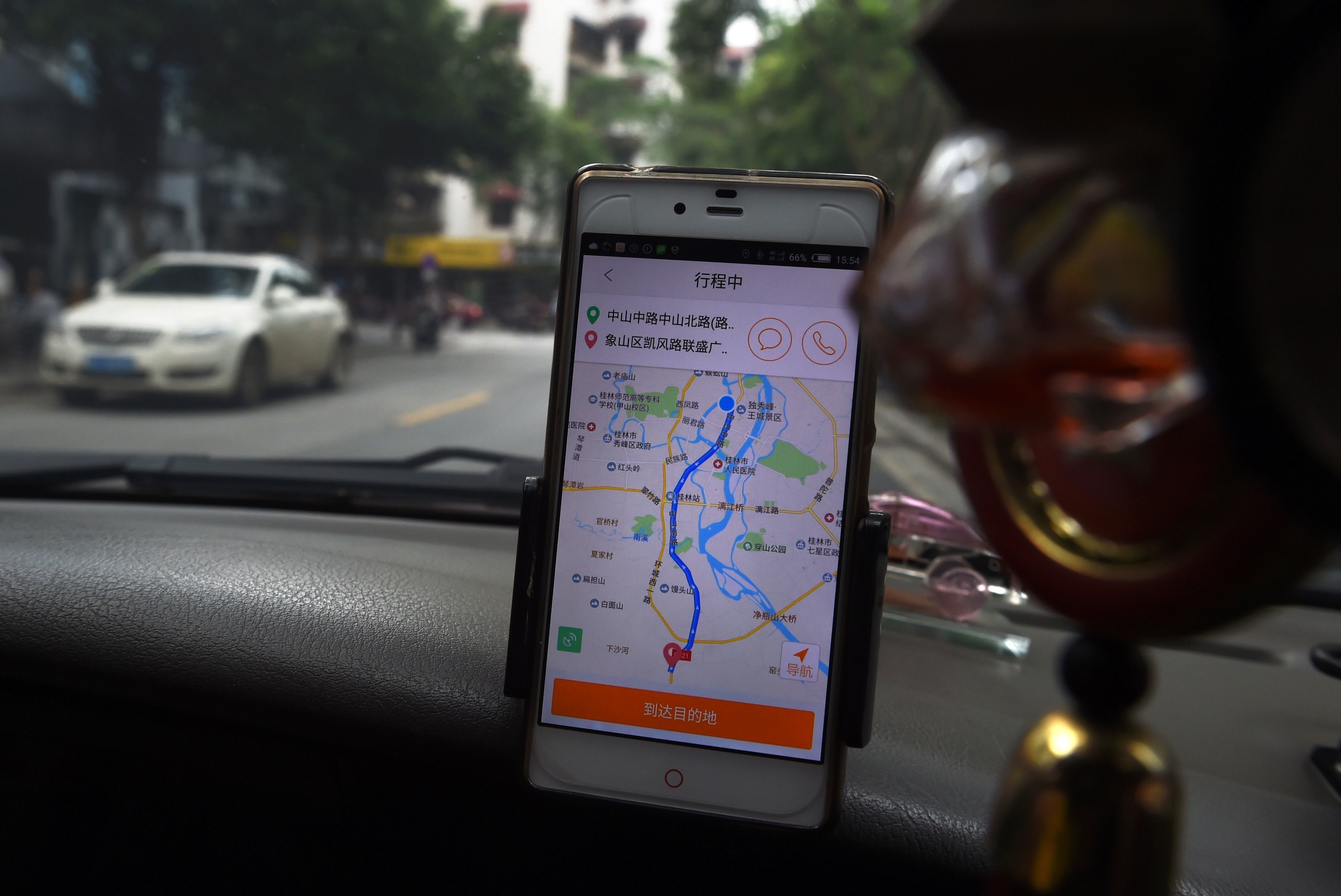 A taxi driver uses the Didi Chuxing app while driving along a street in Guilin, in China's southern Guangxi region on May 13, 2016. Apple has invested 1 billion USD in Chinese ride hailing app Didi Chuxing, the Beijing company said on May 13, as it vies with bitter US-based rival Uber for market share in China. / AFP / GREG BAKER        (Photo credit should read GREG BAKER/AFP/Getty Images)