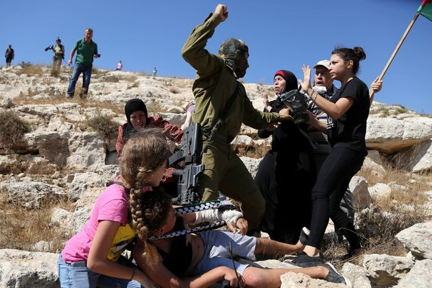 Israeli soldier prepares to strike Palestinians after they interfered with an attempt to arrest a