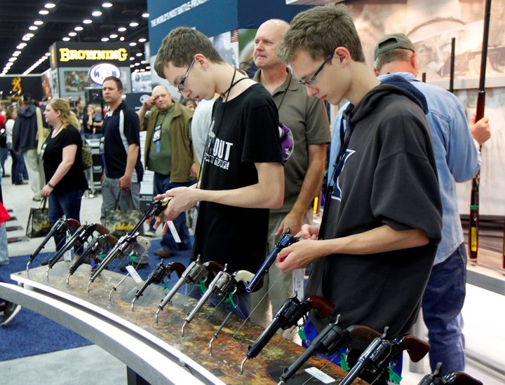 Gun enthusiasts look over Benelli USA guns at the National Rifle Association's (NRA) annual meetings & exhibits show in L